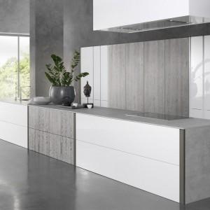 Piękna, nowoczesna kuchnia z bardzo dużą, dwukolorową wyspą kuchenną. Minimalistyczna forma mebla idealnie komponuje się z gładkimi frontami w  bieli i drewnianym dekorze oraz z blatem utrzymanym w szarości, imitującej beton. Fot. Rational, kuchnia Tio Zen.
