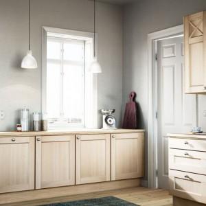 Meble w kolorze jasnego drewna pięknie komponują się z szarością na ścianach. Fronty mebli są delikatnie zdobione, w przypadku gónych szafek również udekorowane szprosami. Drzwiczki dodatkową zdobią estetyczne, okrągłe uchwyty. Fot. Ballingslov, linia Nordic.