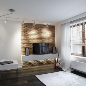 Cegła na ścianie była ręcznie wyrabiana. Stanowi ona estetyczne urozmaicenie w przeważająco białym pokoju. Ciepłym akcentem jest również drewniana podłoga. Projekt: Marta Pala-Szczerbak. Fot. Piotr Lipiecki.