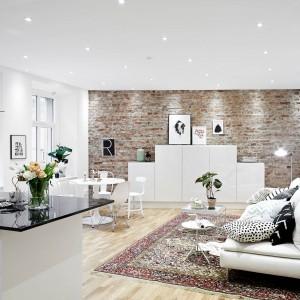 Salon tworzy elegancka biała kanapa i równie biały regał. Przestrzeń wypoczynkową dodatkowo zaznacza obecność klasycznego dywanu oraz czerwona cegła na ścianie. Fot. Stadshem.se.