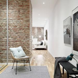 Hol w tym mieszkaniu jest czymś więcej niż ciągiem komunikacyjnym. Jego stylowa, elegancka aranżacja nadaje wytworny charakter całemu mieszkaniu. Cegła na ścianie, metalowy fotel i surrealistyczne obrazy tworzą niezwykle efektowną kompozycję. Fot. Stadshem.se.