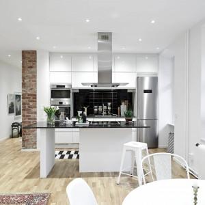 Półwysep poza tym, że pełni funkcję domowego baru i powierzchni do gotowania, symbolicznie wyznacza również granicę pomiędzy funkcjami pomieszczenia. Fot. Stadshem.se.