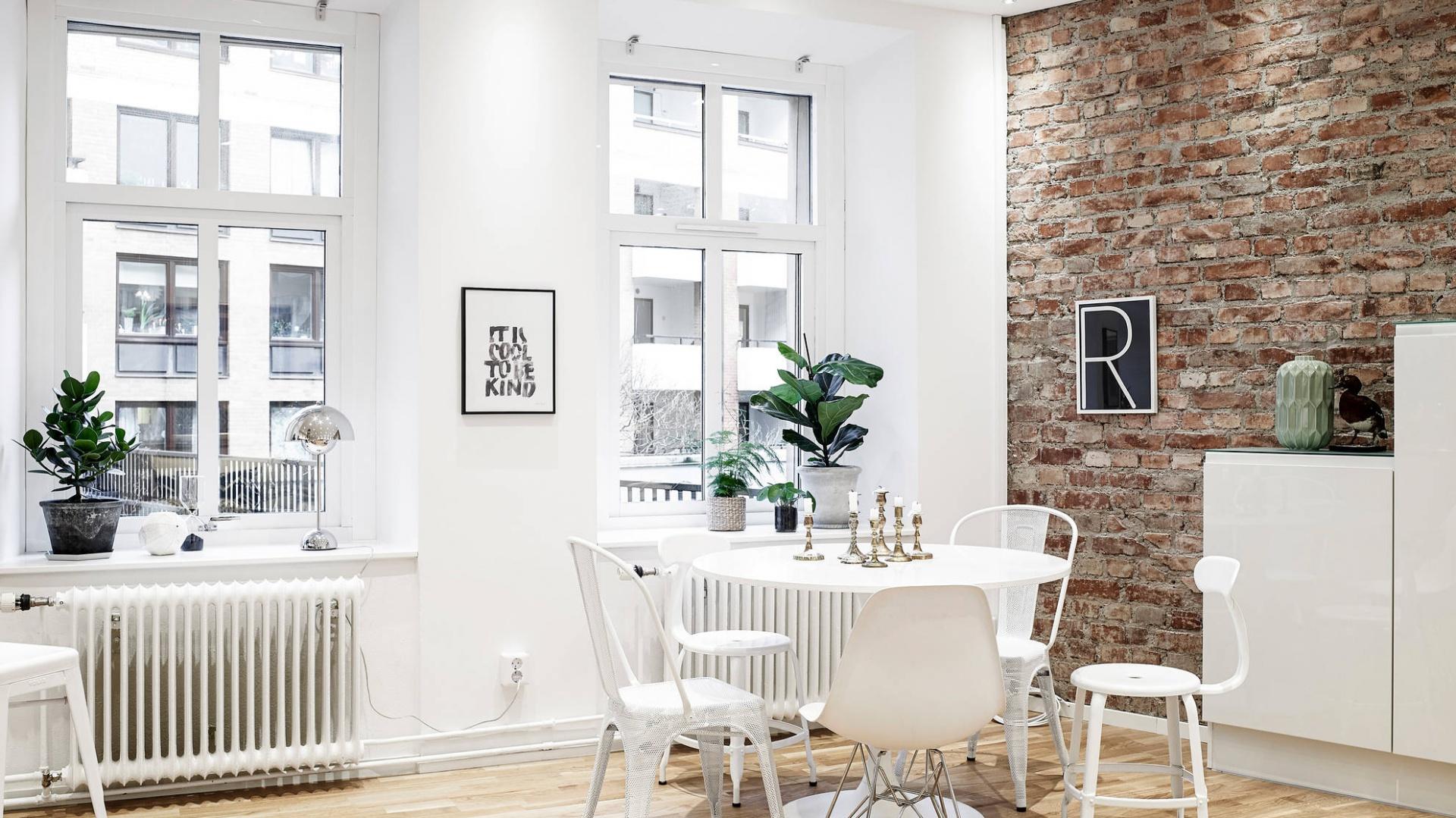 Miejsce na niewielką jadalnię wydzielono w otwartej strefie dziennej. Jej aranżacja - białe krzesła oraz stół - doskonale wpisuje się w styl i charakter wnętrza. Fot. Stadshem.se.
