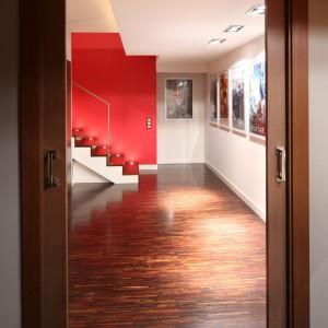 Do salonu kinowego prowadzi klatka schodowa, przysłonięta szklaną ściana w stalowej konstrukcji. Dzięki takiemu rozwiązaniu możemy podziwiać piękne, drewniane schody na tle czerwonej ściany. W stopnicach zamontowano reflektorki świetlne ułatwiające poruszanie się po zmroku. Fot. Bartosz Jarosz.Projekt: Małgorzata Szajbel-Żukowska, Maria Żychniewicz. Fot. Bartosz Jarosz.