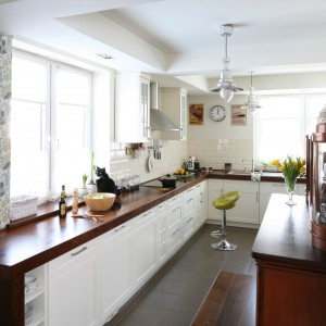 Stalowa barwa oświetlenia koresponduje z kolorystyką kwiecistej tapety, zdobiącej ścianę w kuchni. Projekt: Magdalena Misaczek. Fot. Bartosz Jarosz.
