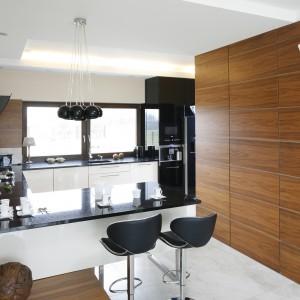 W kuchni występują dwa rodzaje oświetlenia: czysto techniczne, oświetlające blat roboczy oraz dekoracyjne nad półwyspem. Czarne perły na granicy wnętrza wzbogacające przestrzeń ciekawą formą. Projekt: Piotr Stanisz. Fot. Bartosz Jarosz.