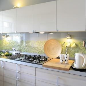 W jasnej, delikatnej kuchni ścianę nad blatem pomalowano szarą farbą. Aby jednak zapobiec nudzie, powierzchnię dodatkowo udekorowano wzorami z zielonego filcu. Przed zabrudzeniami i wysoką temperaturą chroni je szklana tafla. Projekt: Marta Kruk. Fot. Bartosz Jarosz.