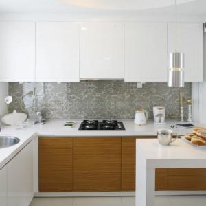 Piękna, elegancka kuchnia, w której ścianę nad blatem pokrywa wzorzysta tapeta o srebrno-szarej barwie. Ścianę zabezpiecza szklany panel. Projekt: Małgorzata Mazur. Fot. Bartosz Jarosz.