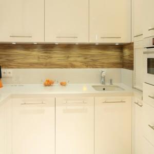 Jasną kuchnię pięknie ociepli drewniany dekor. Tutaj obecny jest w formie laminowanej płyty. Ścianę pokrywają dwa pasy - drugi wykonany z kamienia. Projekt: Małgorzata Galewska. Fot. Bartosz Jarosz.