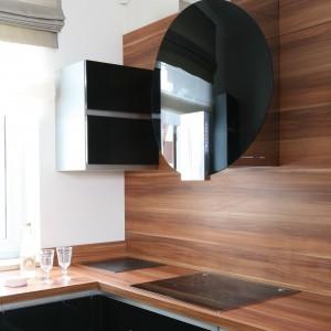 Ściana nad blatem będąca przedłużeniem samego blatu to zabieg aranżacyjny, nadający kuchni elegancki wyraz i styl. Tutaj obie powierzchnie zdobi poziomy, drewniany dekor. Projekt: Karolina Łuczyńska. Fot. Bartosz Jarosz.