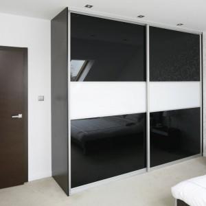 Wysoka zabudowa pełni funkcję pojemnej garderoby. Przesuwne drzwi pozwalają zaoszczędzić miejsce we wnętrzu. Fot. Bartosz Jarosz.