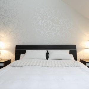 Po obu stronach łóżkach na szafkach nocnych umieszczono lampki o klasycznej formie. Materiałowy abażur i dekoracyjna podstawa lampki dodają wnętrzu elegancji. Fot. Bartosz Jarosz.