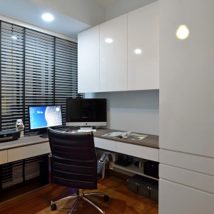 W gabinecie postawiono na funkcjonalność. Biurko poprowadzono wzdłuż ścian, zapewniając maksimum miejsca do pracy. Szafki wykończono na wysoki połysk, rozjaśniając wnętrze i powiększając je optycznie. Z chłodem frontów kontrastuje ciepła, drewniana podłoga. Projekt: KNQ Associates. Fot. KNQ Associates.