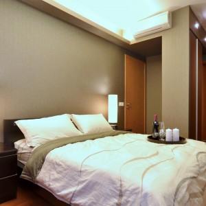 Duża sypialnia w hotelowym stylu to królestwo beżów i brązów. Ciepłe barwy budują przytulną atmosferę w tym zakątku, służącym do relaksu. Projekt: KNQ Associates. Fot. KNQ Associates.