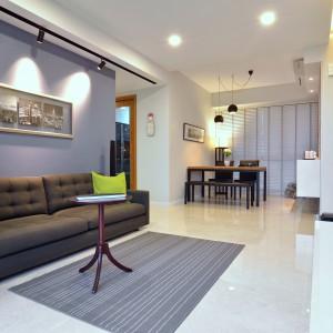 Przestrzeń dzienna to prostota aranżacji i harmonia barw. Kolor dywanu pięknie koresponduje z barwą ściany za kanapą. Ta również została utrzymana w szarościach, choć w znacznie ciemniejszej tonacji. Dominację szarości przełamują dwie poduszki dekoracyjne w kolorze limonki. Projekt: KNQ Associates. Fot. KNQ Associates.