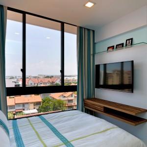 W mniejszej sypialni króluje połaczenie turkusów z bielą. Ocieplającym motywem jest niewielka, drewniana półka pod telewizorem. Całość zorganizowano w oparciu o geometryczne wzory - prostokątne płyty na ścianie, pasy na zasłonach czy ciemne, wyeksponowane na tle nieba, ramy okien. Projekt: KNQ Associates. Fot. KNQ Associates.