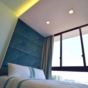Zagłówek zamontowane na pasie zabudowy, kontynuowanym na suficie, w formie podwieszanego sufitu, w którym zamontowano oświetlenie. Projekt: KNQ Associates. Fot. KNQ Associates.