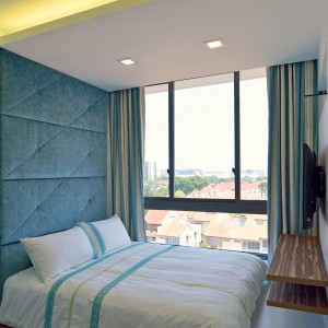 Pikowany zagłówek wprowadza element przytulności do wnętrza, w którym królują chłodne barwy. Wtórują mu drewniana podłoga i półka na ścianie. Projekt: KNQ Associates. Fot. KNQ Associates.