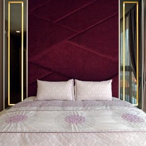 Po obu stronach tekstylnego zagłówka poprowadzonego niemal pod sam sufit, zlokalizowano długie, pionowe lustra, ozdobione przy krawędziach dekoracjami w kolorze złota. Projekt: KNQ Associates. Fot. KNQ Associates.