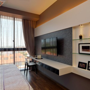 Ścianę na przeciwko dużego łóżka pokrywa zabudowa z praktycznym, niewielkim biurkiem i kilkoma delikatnymi półkami. W centrum znalazł się natomiast telewizor. Projekt: KNQ Associates. Fot. KNQ Associates.