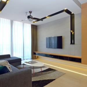 Podwieszany sufit w salonie i zabudowa za telewizorem posłużyły za bazę na stworzenie oryginalnych elementów aranżacji wnętrza. Czarne wnęki na suficie to miejsce zamontowania oświetlenia, a jedna z nich płynnie przechodzi w pionowy pas czerni na ścianie, który zakończony został niewielką półeczką. Projekt: KNQ Associates. Fot. KNQ Associates.