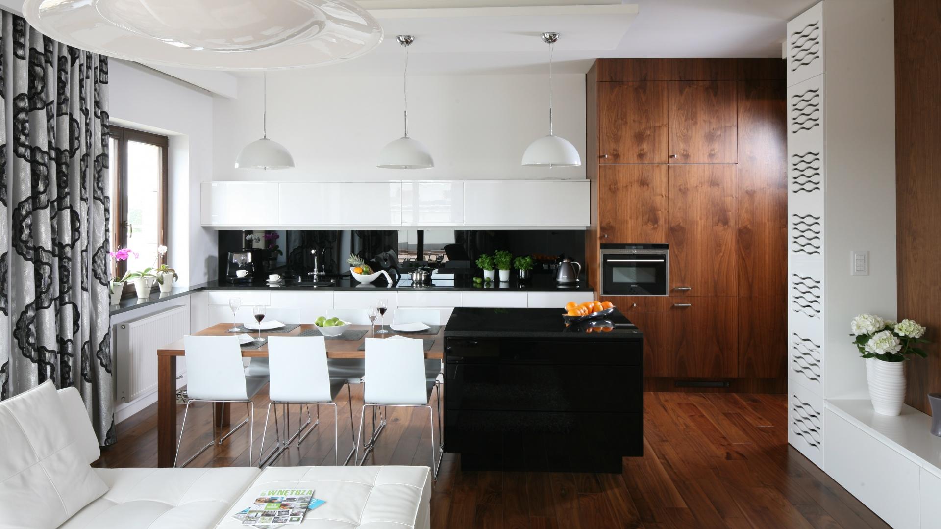 Poprowadzona pod sam sufit wysoka zabudowa zyskała piękny drewniany dekor. Posłużyła za element ocieplający wnętrze, lokalizację montażu piekarnika oraz za pojemne miejsce do przechowywania sprzętów. Projekt: Agnieszka Ludwinowska. Fot. Bartosz Jarosz.