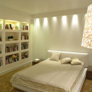 Biblioteczka w sypialni? Czemu nie! Przecież lektura do poduszki to jedna z najprzyjemniejszych rzeczy przed snem. W tej sypialni półki na książki zostały zorganizowane bezpośrednio w ścianie. Ich podświetlenie nadaje wnętrzu przytulności. Projekt: Małgorzata Borzyszkowska. Fot. Bartosz Jarosz.