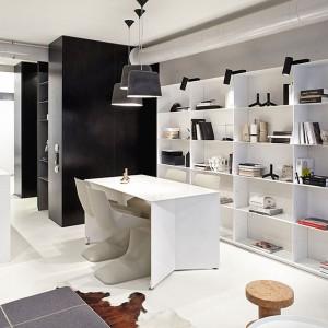 W tym kijowskim apartamencie, opartym na idei open space, jedną ze ścian w całości zabudowano prostymi, białymi regałami. Techniczne oświetlenie nadaje nowoczesnemu rozwiązaniu lekko studyjnego charakteru. Fot. Olga Akulova DESIGN.