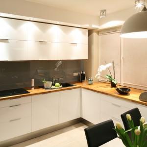 Ciemna ściana jest najmocniejszym detalem w aranżacji kuchni. Nawiązuje kolorystycznie do mebli w sąsiadującej, nieiwlekiej jadalni. Projekt: Lucyna Kołodziejska. Fot. Bartosz Jarosz.
