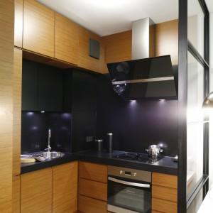 Czarna ściana sprawia, że kuchnia w kolorze drewna zyskuje nowoczesny styl. Blat roboczy wybrano również w tym samym kolorze. Projekt: Michał Dudko. Fot. Bartosz Jarosz.