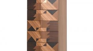 """Komoda """"Maggio"""" pokryta jest abstrakcyjną geometryczną abstrakcyjną mozaiką wykonaną z trzech gatunków drewna (wiąz, dąb i akacja) i posiada wysuwane lustro."""