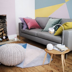 Szara, minimalistyczna sofa na drewnianych nóżkach i designerski stolik kawowy, eksponujący piękny rysunek słojów drewna. Fot. Marks&Spencer.