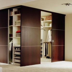 Nie trzeba mieć oddzielnego pomieszczenia na garderobę, żeby ją posiadać. Za pomocą drzwi przesuwnych można wydzielić część sypialni, np. w rogu, żeby zaaranżować praktyczną przestrzeń ze wszelkimi funkcjonalnymi rozwiązaniami. Do tego jednak potrzebna jest dość przestronna sypialnia. Raumplus.