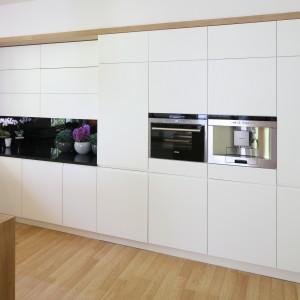 Wpasowana we wnękę w ścianie biała zabudowa kuchenna została zlicowana ze ścianą, w którą ją wbudowano. Zamknięta w brązową ramę prezentuje się nad wyraz elegancko. Projekt: Małgorzata Błaszczak. Fot. Bartosz Jarosz.