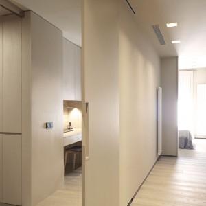 Podział przestrzeni w mieszkaniu oparto na mobilnych rozwiązaniach. Tutaj tradycyjną ścianę przedłużają przesuwne drzwi. Projekt: Coblonal Arquitectura. Fot. Coblonal Arquitectura.