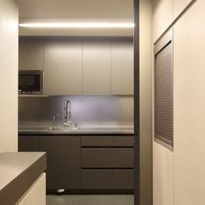 Fronty zabudowy kuchennej wykończono w macie i ciemnej szarości. Eleganckie, gładkie powierzchnie pozbawiono frontów, nadając im minimalistyczny charakter. Wieńczy je stalowy blat, harmonizujący z barwą frontów. Tym samym materiałem wykończono również ścianę nad blatem. Projekt: Coblonal Arquitectura. Fot. Coblonal Arquitectura.