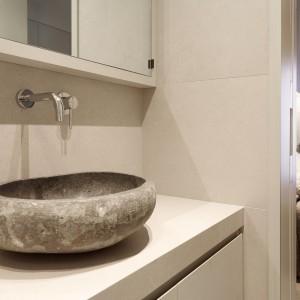 W łazience małżeńskiej, połączonej z sypialnią, uwagę przykuwa piękna, kamienna umywalka nablatowa. Oryginalny design nadaje jasnej, delikatnej łazience lekko surowy charakter. Projekt: Coblonal Arquitectura. Fot. Coblonal Arquitectura.