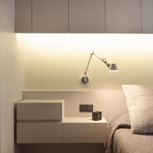 Rolę oświetlenia przy łóżku w sypialni pełni zainstalowana na ścianie lekko industrialna lampka. Osprzęt zamontowano w jasnej zabudowie i utrzymano w kontrastującym z nią, ciemnym kolorze. Projekt: Coblonal Arquitectura. Fot. Coblonal Arquitectura.