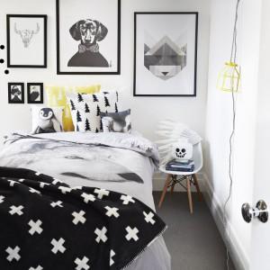 Biało-czarną sypialnię ożywiają żółte dodatki. Delikatna lampka, poduszki i dekoracje wiszące na ścianie również ocieplają wnętrze. Fot. Norsu interior.