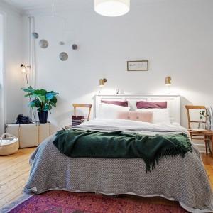 Kolorowa tkaniny silnie wpływają na odbiór wnętrza. Dekoracyjne poduszki, narzuta ocieplają sypialnię. Fot. Alvhem Makleri.