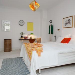 Białe wnętrze ocieplono dodatkami w ciepłej tonacji. Żółty plakat nad biurkiem, pomarańczowa narzuta, czerwona poduszka i wisząca lampa o ciekawiej formie wprowadzają do wnętrza przytulną atmosferę. Fot. Alvhem Makleri.