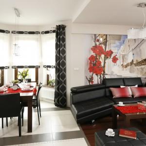 Kuchnia to wnętrze otwarte na jadalnię i salon. Czerwone akcenty dekoracyjne całej części dziennej są nawiązaniem do fototapety przedstawiającej grecką uliczkę i piękne kwiaty. Projekt: Marta Kilan. Fot. Bartosz Jarosz.