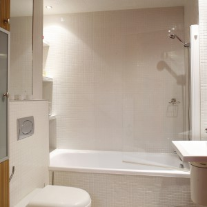 W łazience połączone funkcje dwóch elementów wyposażenia w jednym: z wanny można korzystać jak z kabiny – wygodę zapewnia bateria z rączką prysznicową, ochronę przed zachlapaniem – parawan nawannowy. Projekt: Daniel Niechaj. Fot. Bartosz Jarosz.