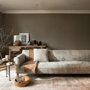 Ciepłe beże i brązy, nawiązujące do natury, stały się tłem dla eleganckiej sofy, której tapicerka stylizowana jest na starą. Fot. Flamant.