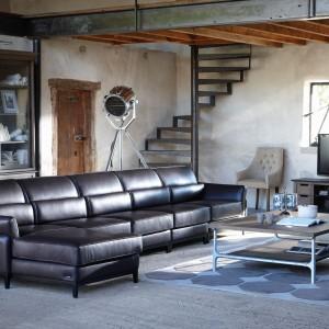 Głównym elementem wystroju salonu jest niezwykle elegancka skórzana sofa. Na tle betonowych ścian oraz stylizowanych mebli prezentuje się naprawdę wyśmienicie. Fot. Grange.