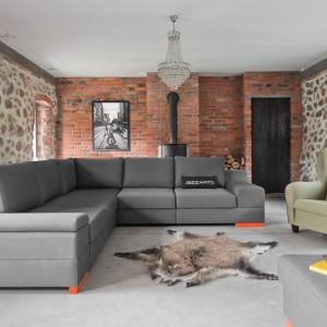 Szary modułowy narożnik o nowoczesnej formie i pomarańczowych nóżkach idealnie prezentuje się na tle starej, ceglanej ściany. Fot. Bizzarto.