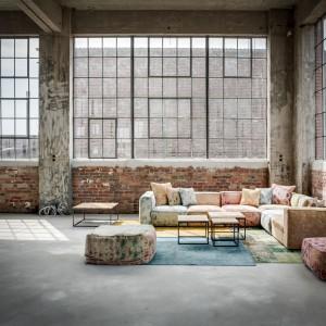 Nowoczesna, multikolorowa sofa modułowa, której tapicerowane w tkaninie obicie stylizowane przyciąga uwagę feerią barw, doskonale wpisała się w stare, pofabryczne wnętrze. Fot. Maison objets.