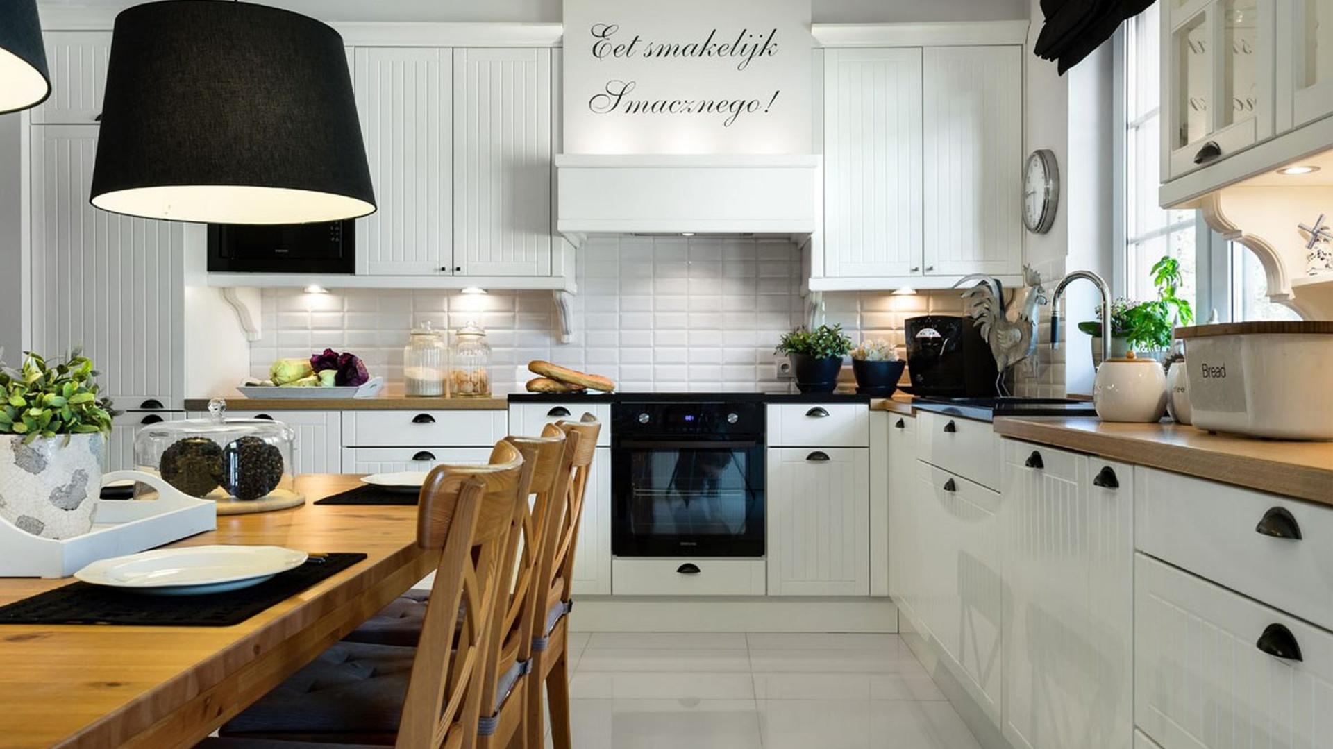 Blaty kuchenne zostały wykonane w dwóch kolorach i materiałach. Połączono tutaj czarny granit oraz laminat dębowy. Czerń komponuje się z ozdobnymi uchwytami na białych drzwiczkach, a laminat imitujący drewno ociepla przestrzeń. Fot. Pracownia Mebli Vigo, kuchnia Navia.