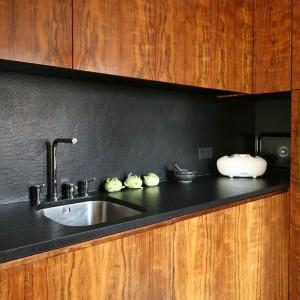 W tej oryginalnej, odważnej kuchni, zainspirowanej amerykańskim stylem lat 50-tych, blat i powierzchnia nad nim są wykończone tym samym materiałem. Z egzotycznym drewnem kontrastuje efektownie czarny granit. Projekt: Katarzyna i Michał Dudko. Fot. Bartosz Jarosz.