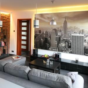 Jedną ze ścian nowoczesnego, nieco loftowego salonu ozdobiono panoramiczną fototapetą. Aby wyeksponować walory tej dekoracji, zdecydowano się podświetlić ją ledami. Projekt: Katarzyna Karpińska-Piechowicz. Fot. Bartosz Jarosz.